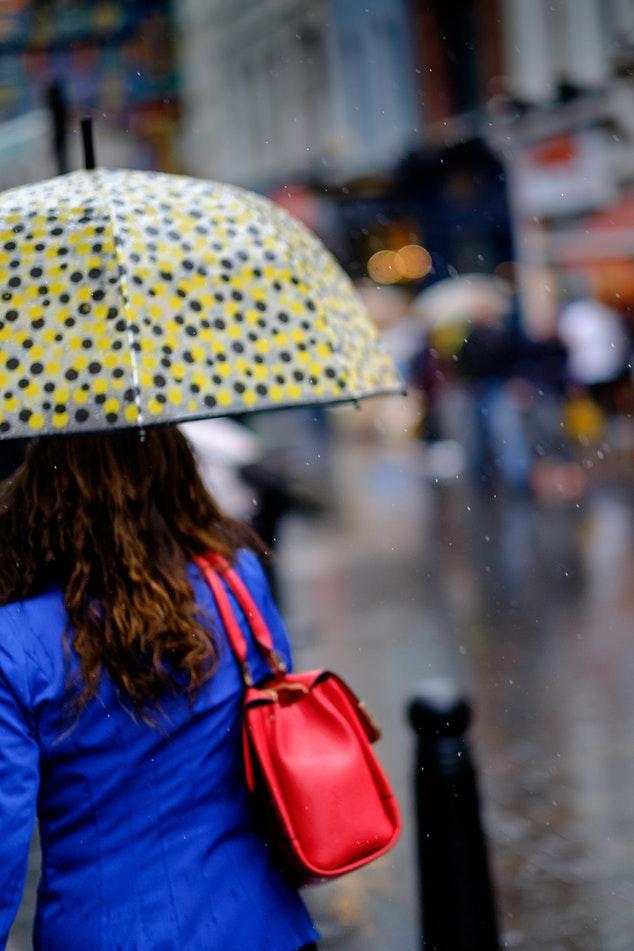 Femeie cu o geanta roșie ține o umbrelă în mână.